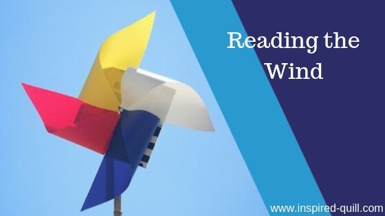 A blog feature image showing a colourful pinwheel against a blue sky and the title 'Reading the Wind' over the top