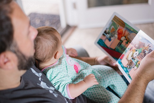 A father reading a picture book to a baby sitting on his knee