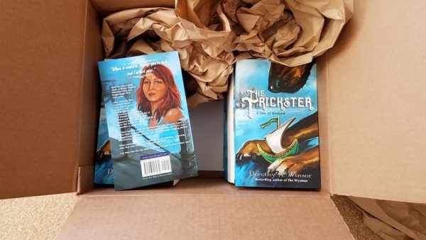 A box of books with copies of the YA fantasy novel The Trickster